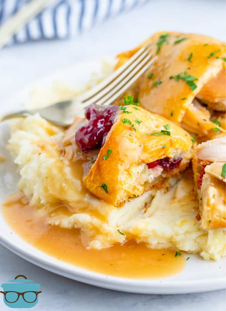 Turkey and Stuffing Crescent Roll Bundles served on top of mashed potatoes with gravy on top