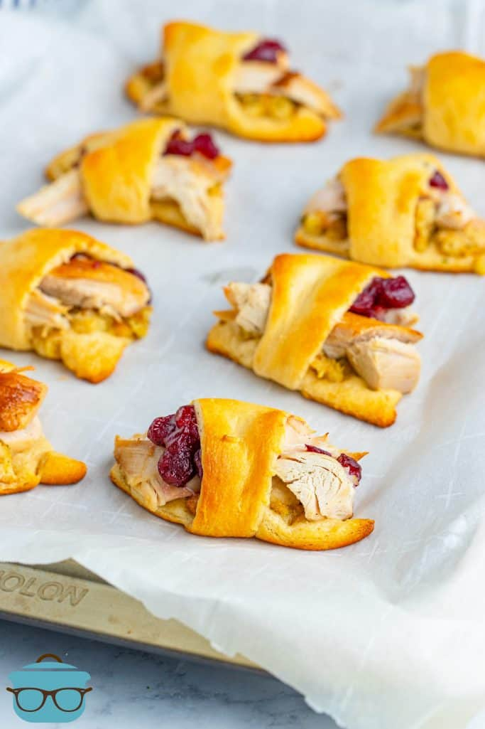 Leftover Turkey Crescent Roll Ups shown fully baked on parchment paper