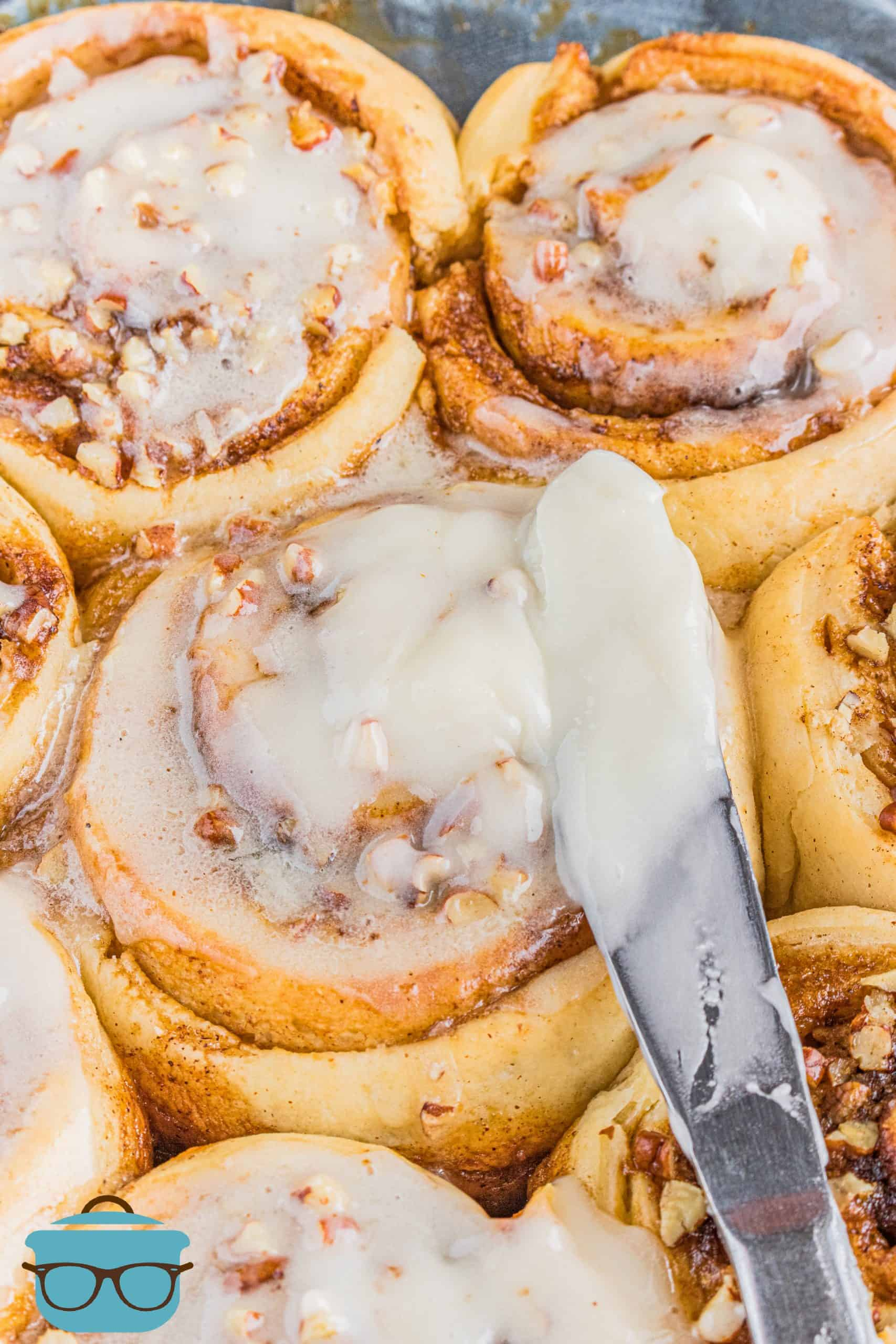 cream cheese frosting spread onto cinnamon rolls with a butter knife