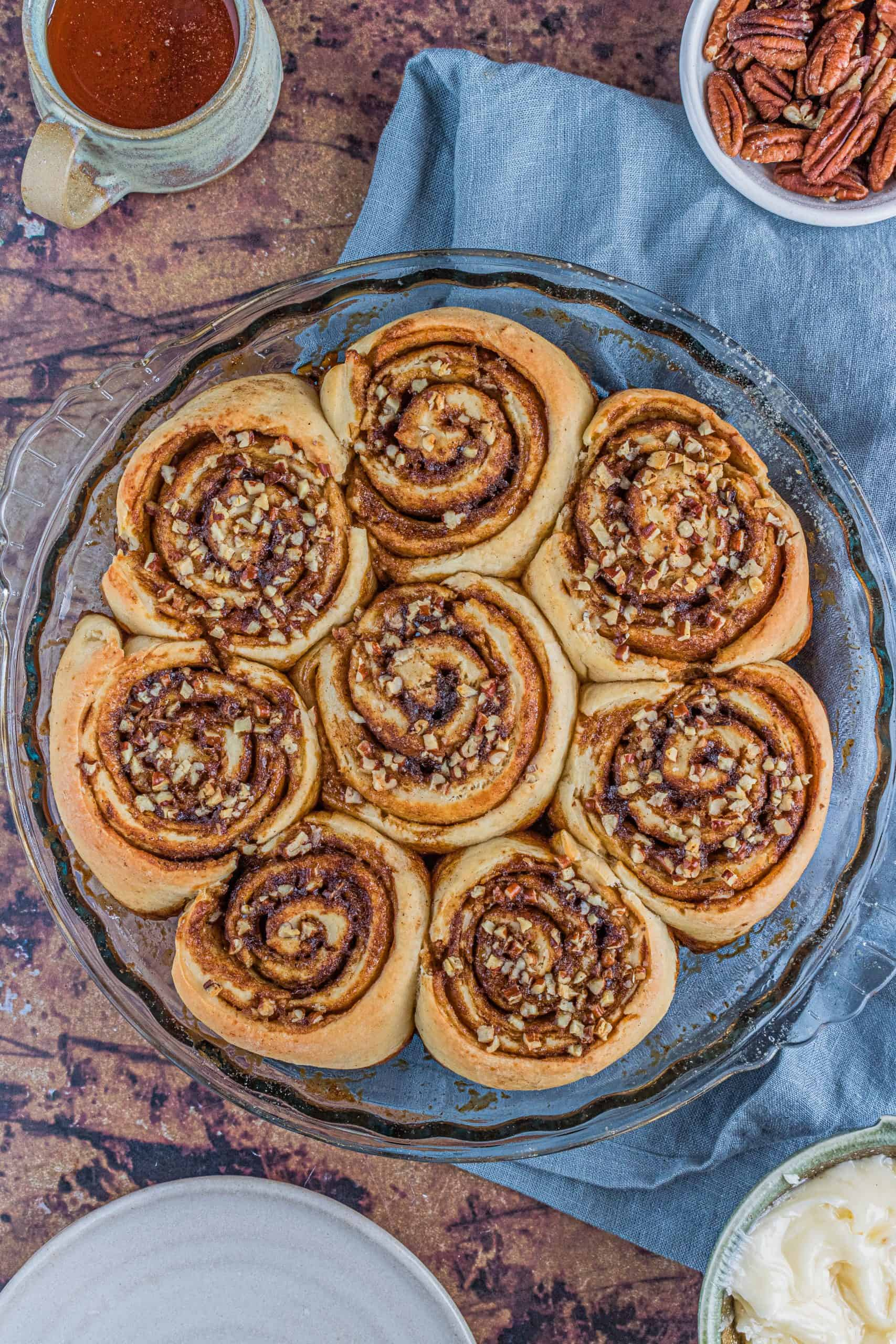 baked pecan cinnamon rolls in a clear pie dish