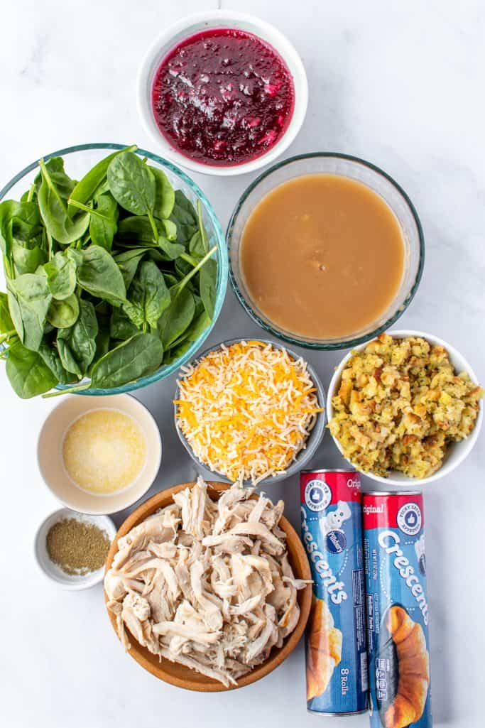 crescent rolls, shredded turkey, stuffing, spinach leaves, cranberry sauce, Monterey Jack cheese, melted butter, poultry seasoning, turkey gravy