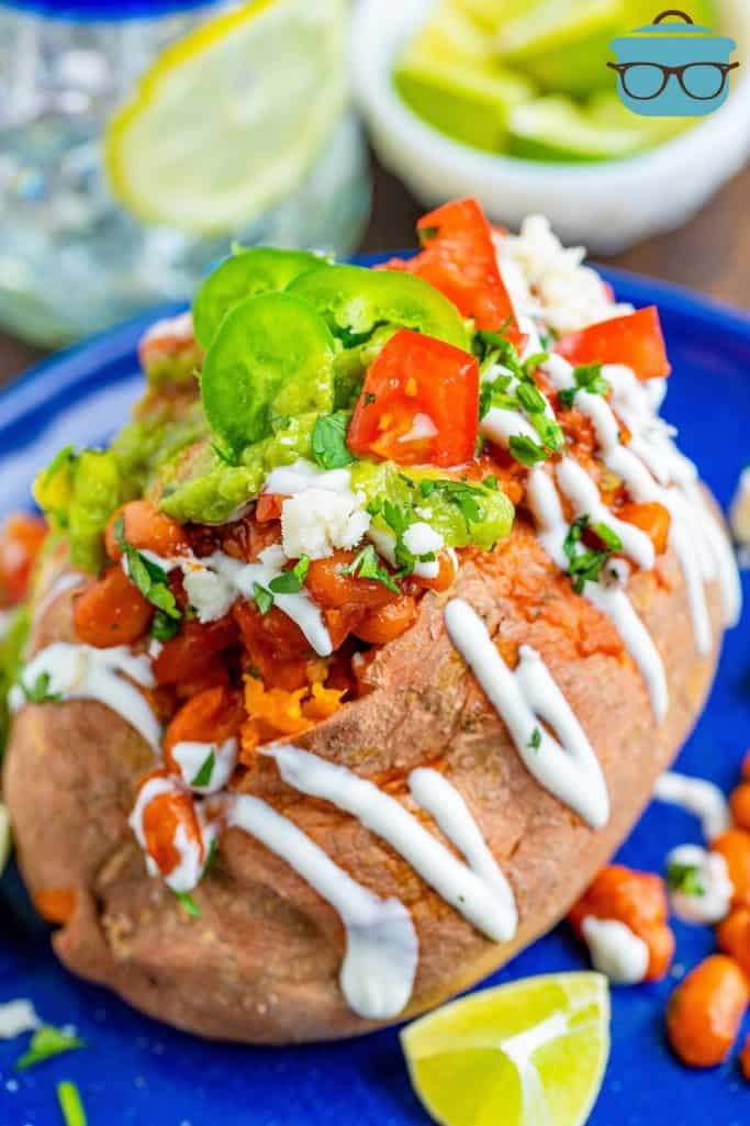 bean stuffed sweet potatoes topped with sour cream, guacamole, diced tomatoes and guacamole