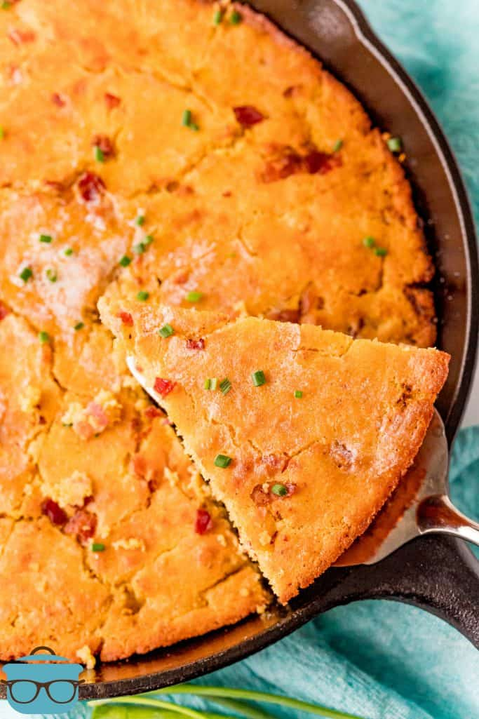 Bacon Cornbread in a cast iron, sliced into 8 pieces, with a pie server scooping out one piece