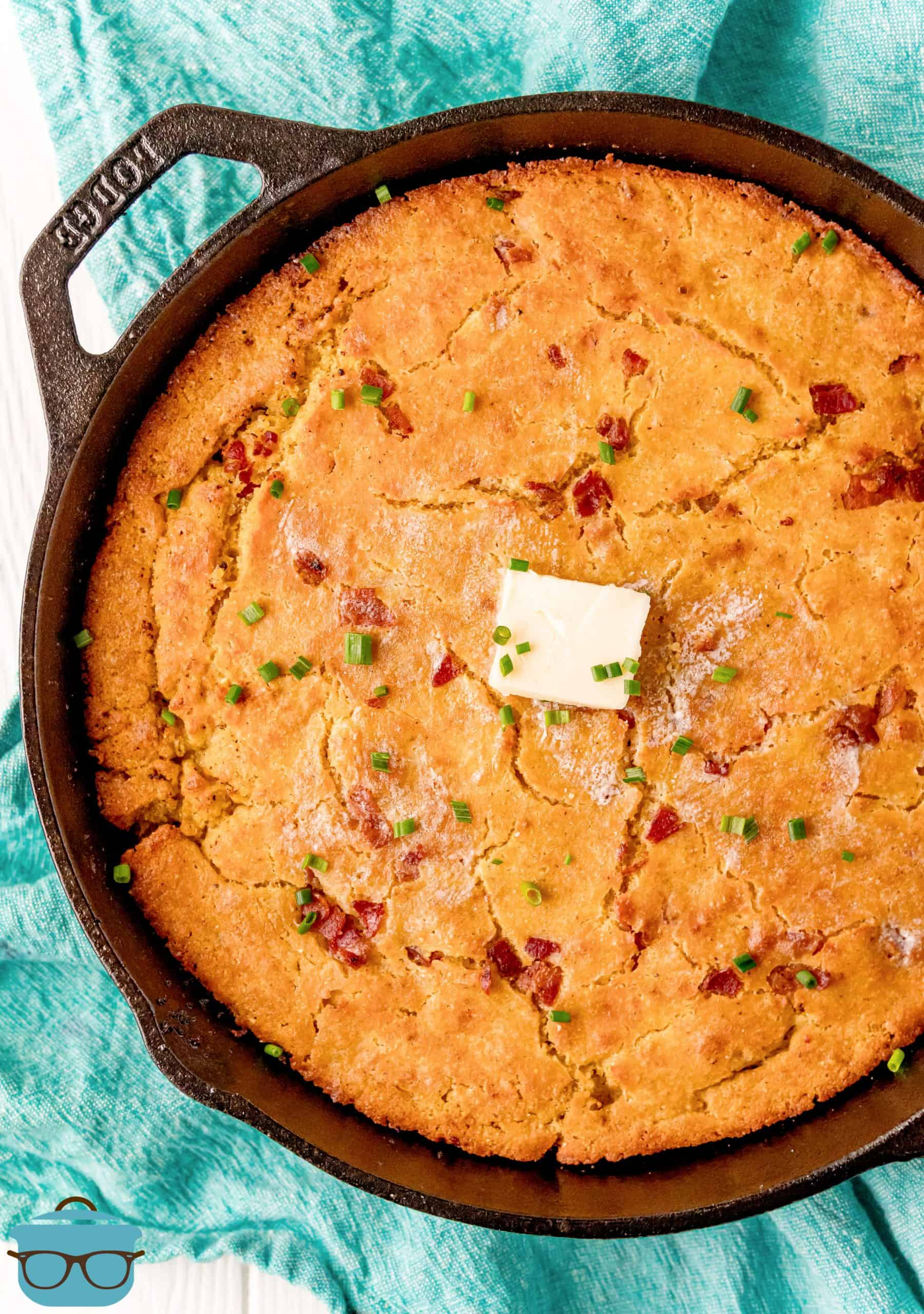 fully baked bacon cornbread in a cast iron skillet with a pat of butter on top