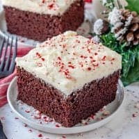 Homemade Chocolate Peppermint Cake, slice of cake shown on a small white round plate with christmas decor the background