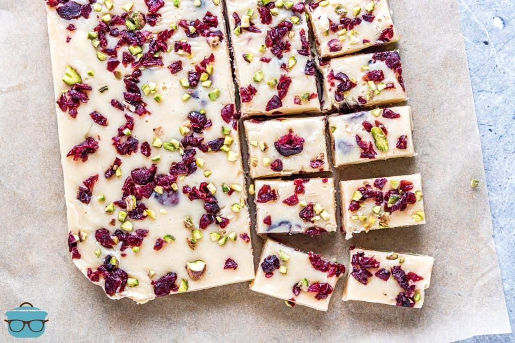 Cranberry Pistachio Fudge cortado em quadrados em papel pergaminho de cor natural