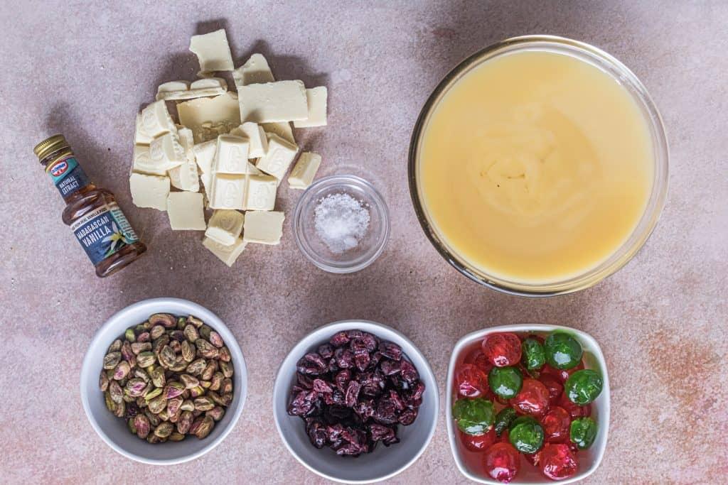 leite condensado adoçado, barras de chocolate branco, extrato de baunilha, sal, cerejas verdes e vermelhas glaceadas, cranberries secas, pistache com casca