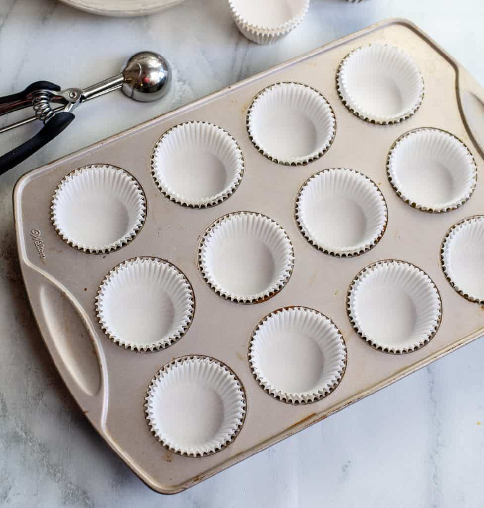 paper liners added to the cupcake pan with a scooper off to the side