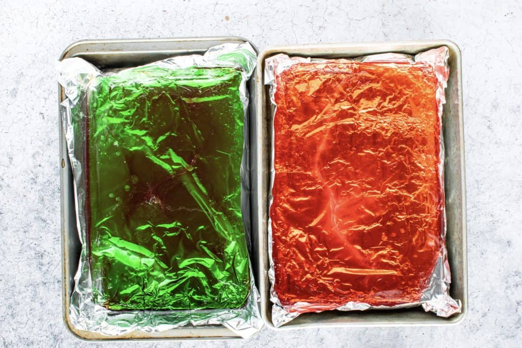 red and green liquid rock candy poured into two separate pans lined with aluminum foil