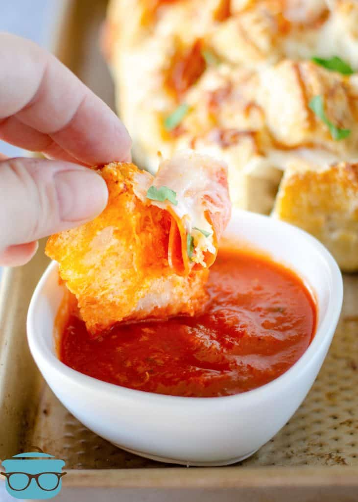 a slice of pepperoni bread being dipped in pizza sauce that is in a small white bowl