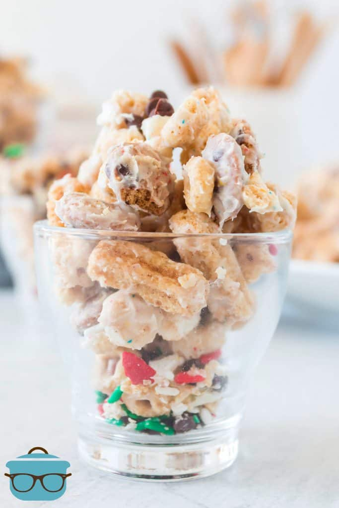 Christmas White Trash Snack Mix in a small clear shot glass on a white surface