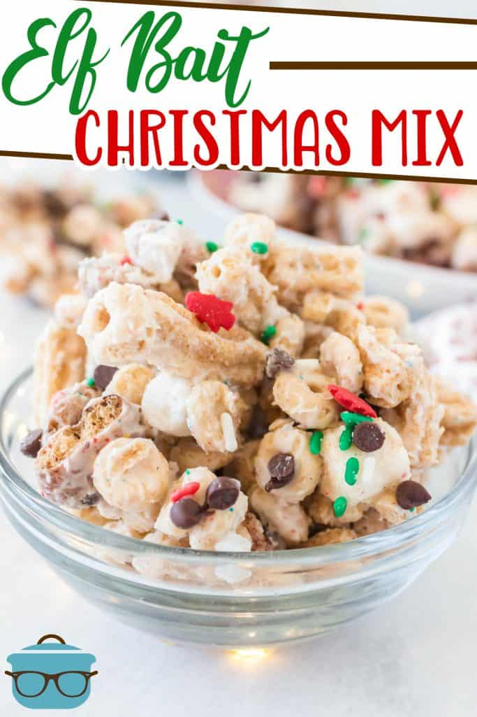 Elf Bait Christmas Mix recipe from The Country Cook, snack mix shown in a clear bowl with small twinkling lights in the background