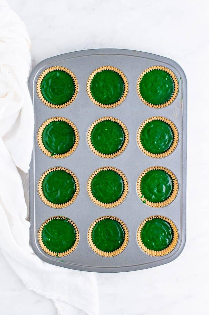 muffin tin with cupcake liners filled with green velvet cupcake batter