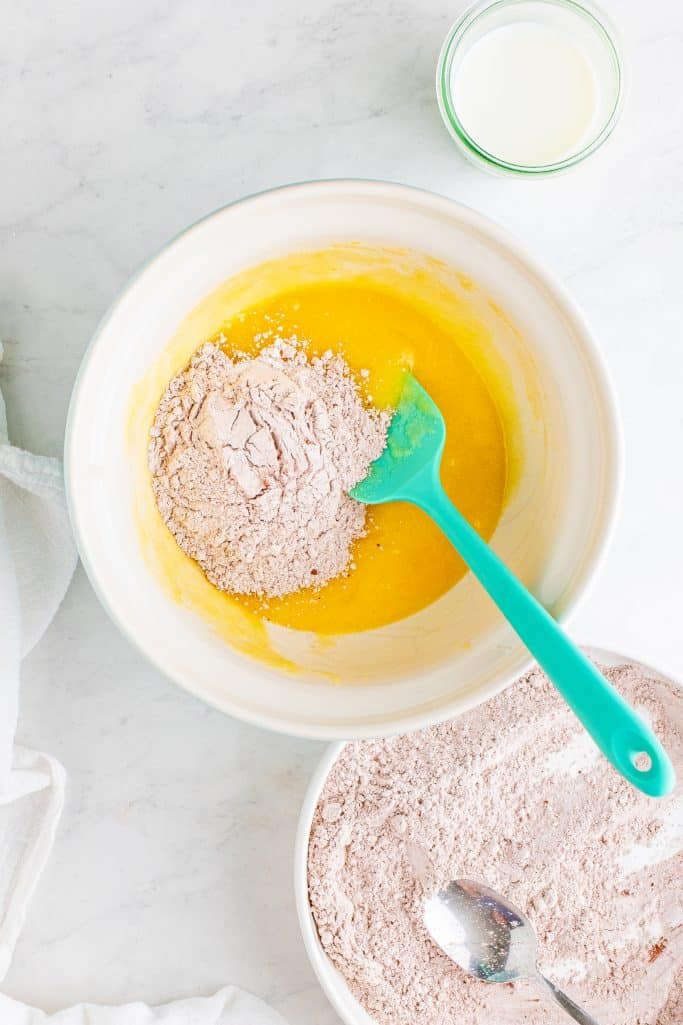 cocoa flour mixture added to liquid butter mixture in a white bowl with a turquoise rubber spoon