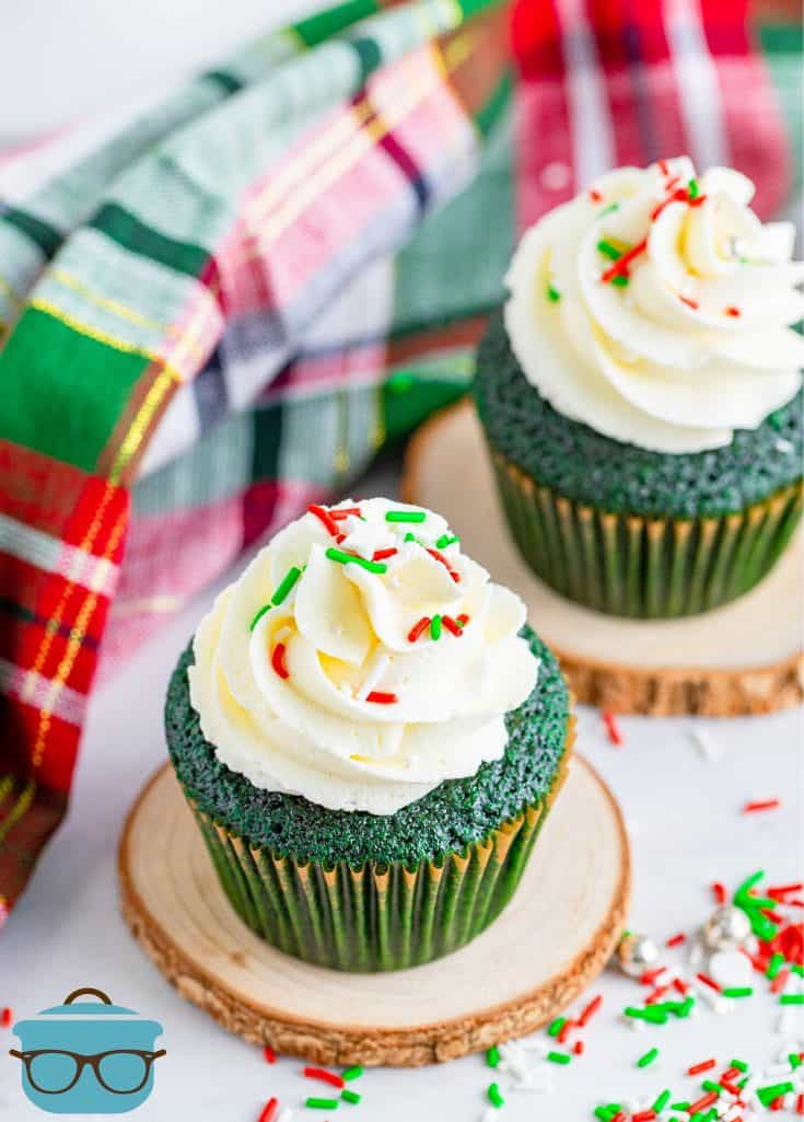 two green velvet cupcakes with buttercream frosting displayed on two small circular wooden discs with a plaid dish towel in the background