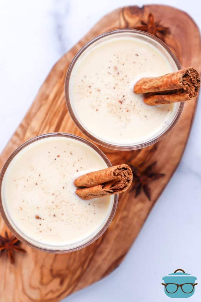 Instant Pot Egg Nog shown in two small, clear glasses with sticks of cinnamon in each glass shown on a wooden cutting board