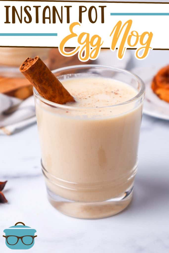 Instant Pot Egg Nog recipe from The Country Cook, pictured in a small glass with a cinnamon stick, shown on a marble surface