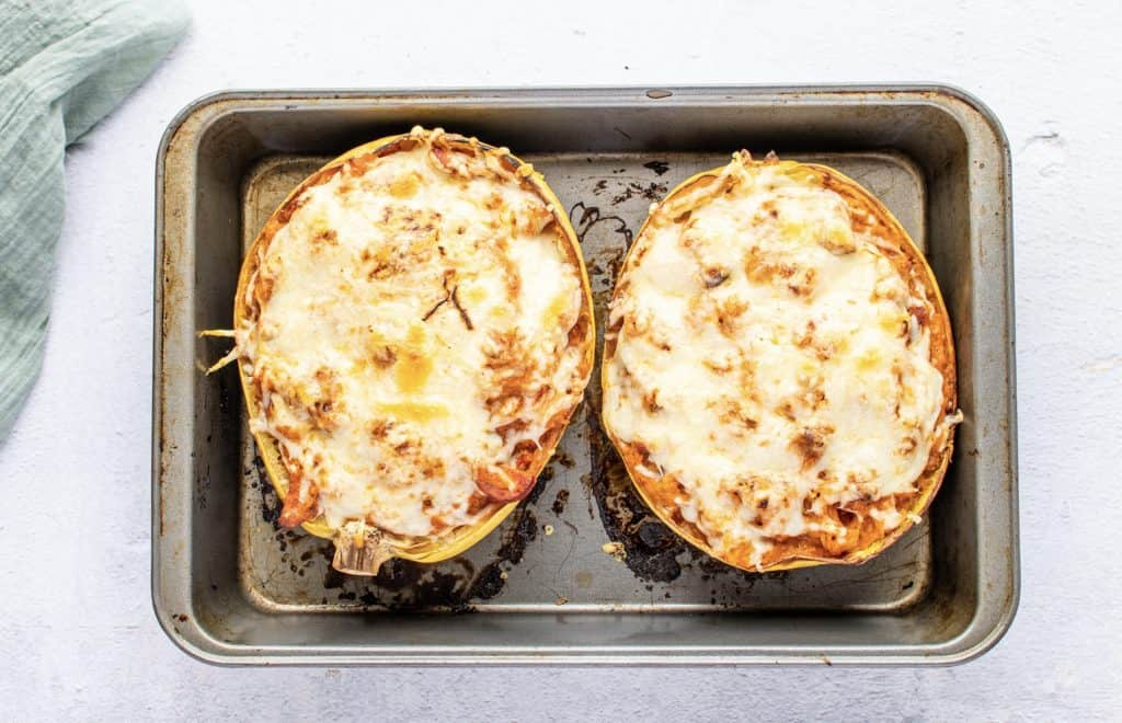 fully baked stuffed spaghetti squash topped with melted mozzarella cheese shown on a metal baking sheet