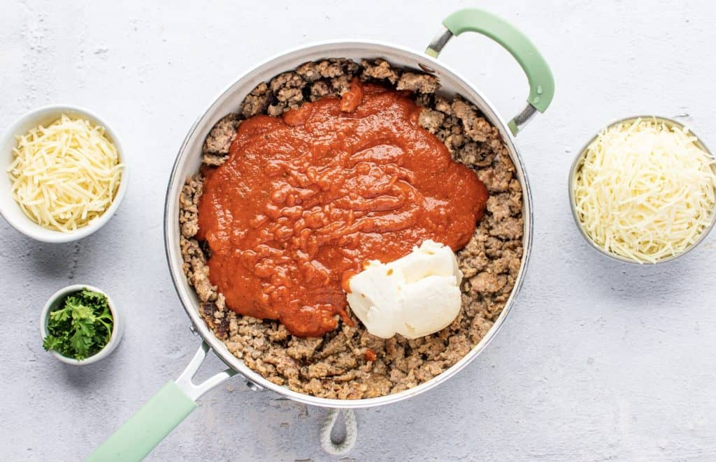 ground sausage and kielbasa in a large skillet with marinara sauce and ricotta on top