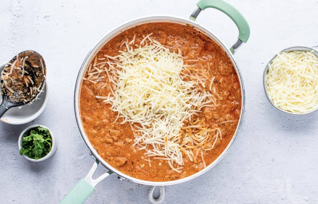 shredded Parmesan and mozzarella cheese on top of Italian sausage sauce in a skillet