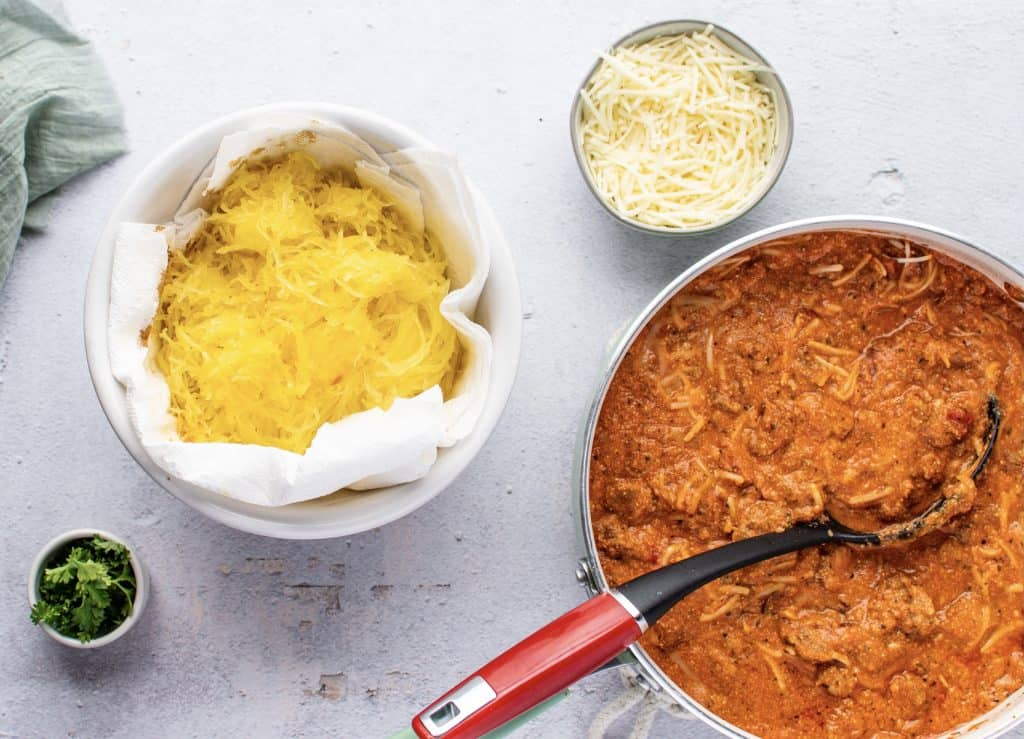 shredded spaghetti squash in a b owl lined with paper towels to remove excess liquid from squash