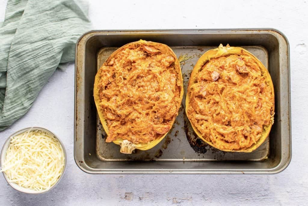 slices of spaghetti squash filled with Italian sauce mixture on a baking sheet