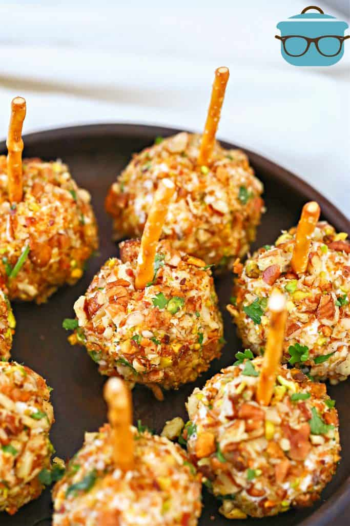Easy Mini Pecan Coated Cheeseball appetizers with pretzel sticks shown on a black, circle platter