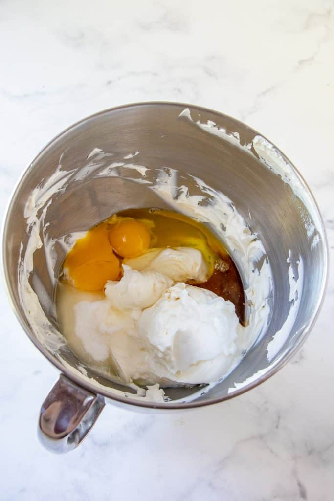 eggs, sour cream and vanilla extract added to cream cheese in a bowl