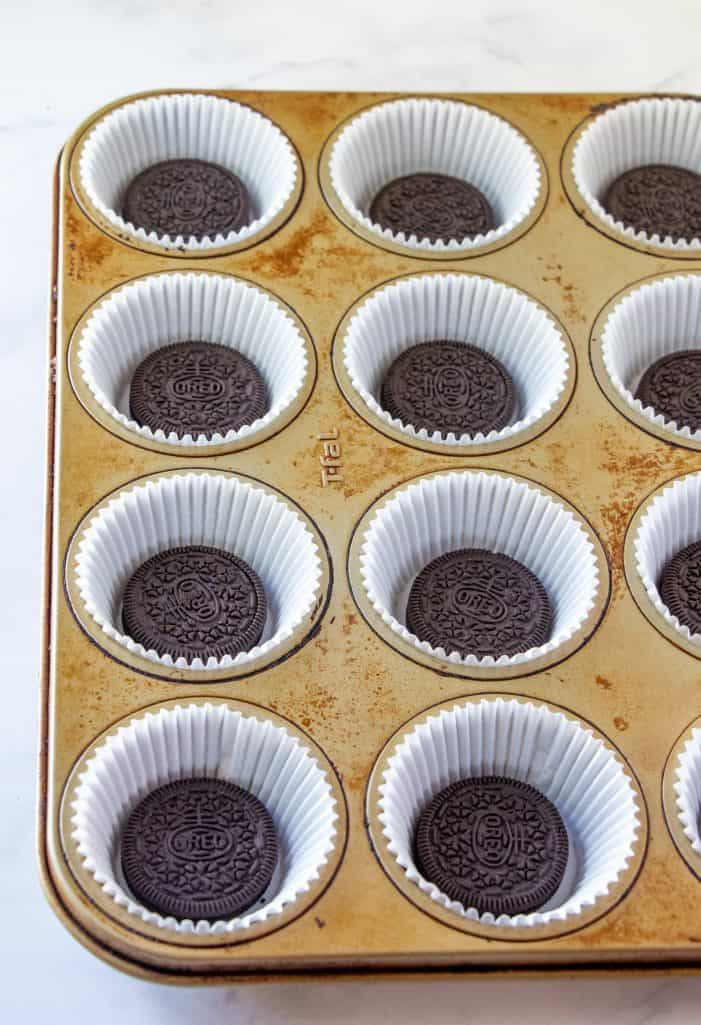 Oreo cookies placed into the bottom of paper cupcake liners in a muffin tin