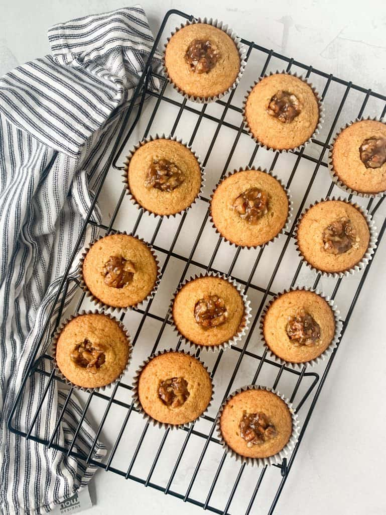 pecan pie filling dolloped into the center of the pecan cupcakes sitting on a black cooling rack
