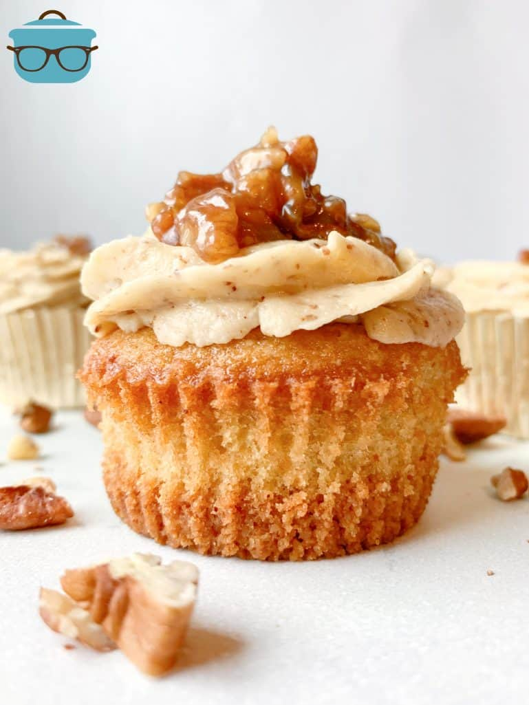 single pecan pie cupcake shown without a cupcake liner, chopped pecans sprinkled around the cupcake