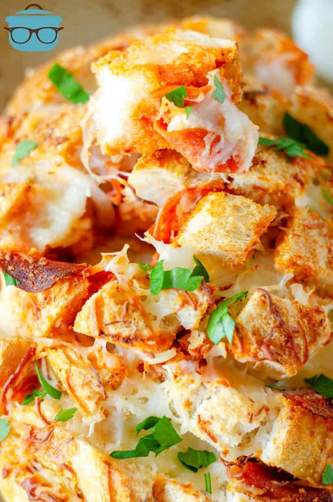 Cheesy pull apart bread with pizza sauce shown close up with chopped parsley