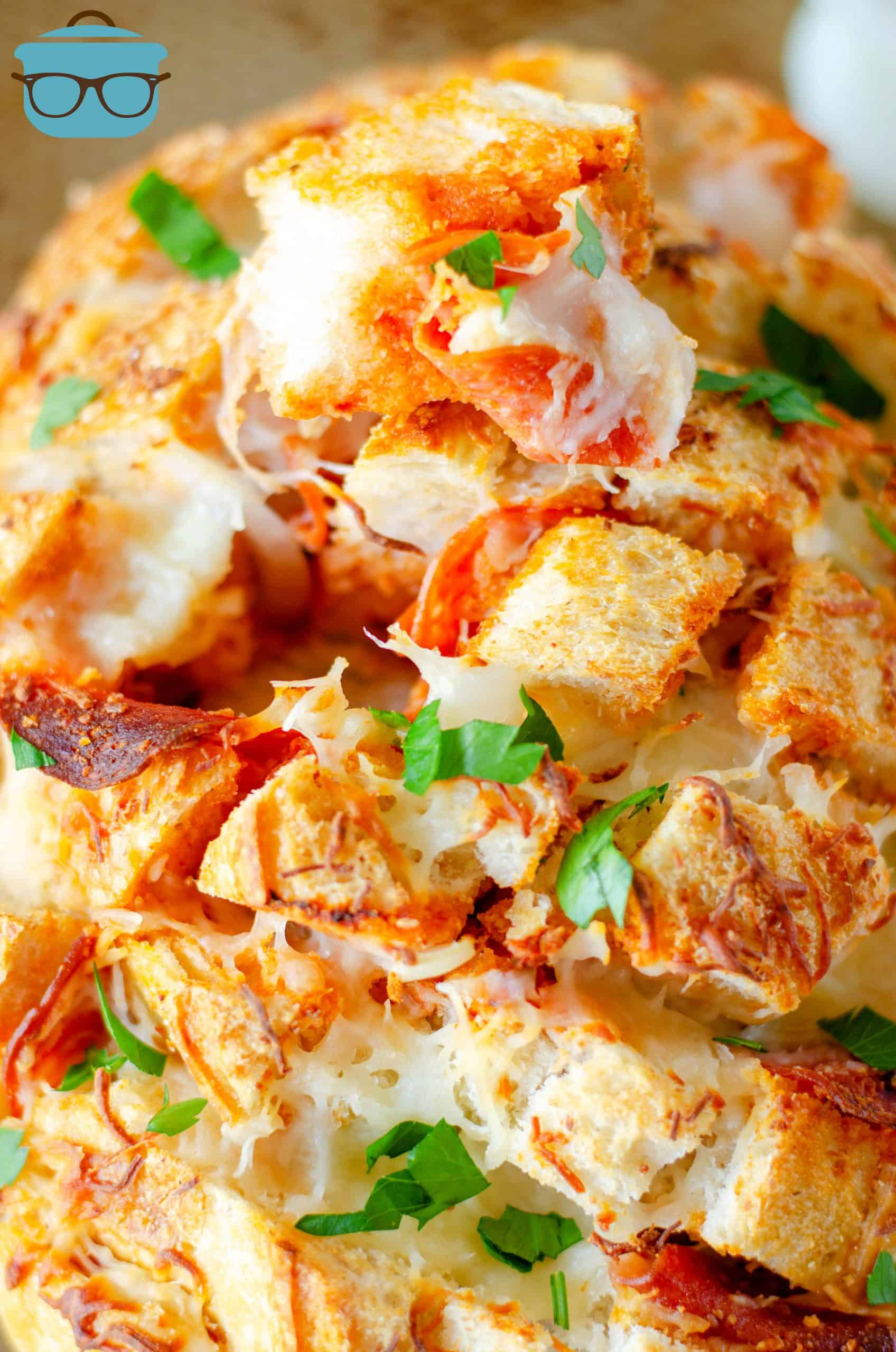 Cheesy pull apart bread with pizza sauce shown close up with chopped parsley.