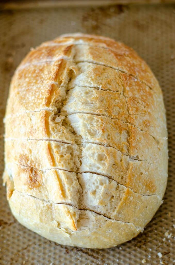oval loaf of sourdough bread shown with diagonal cuts across it