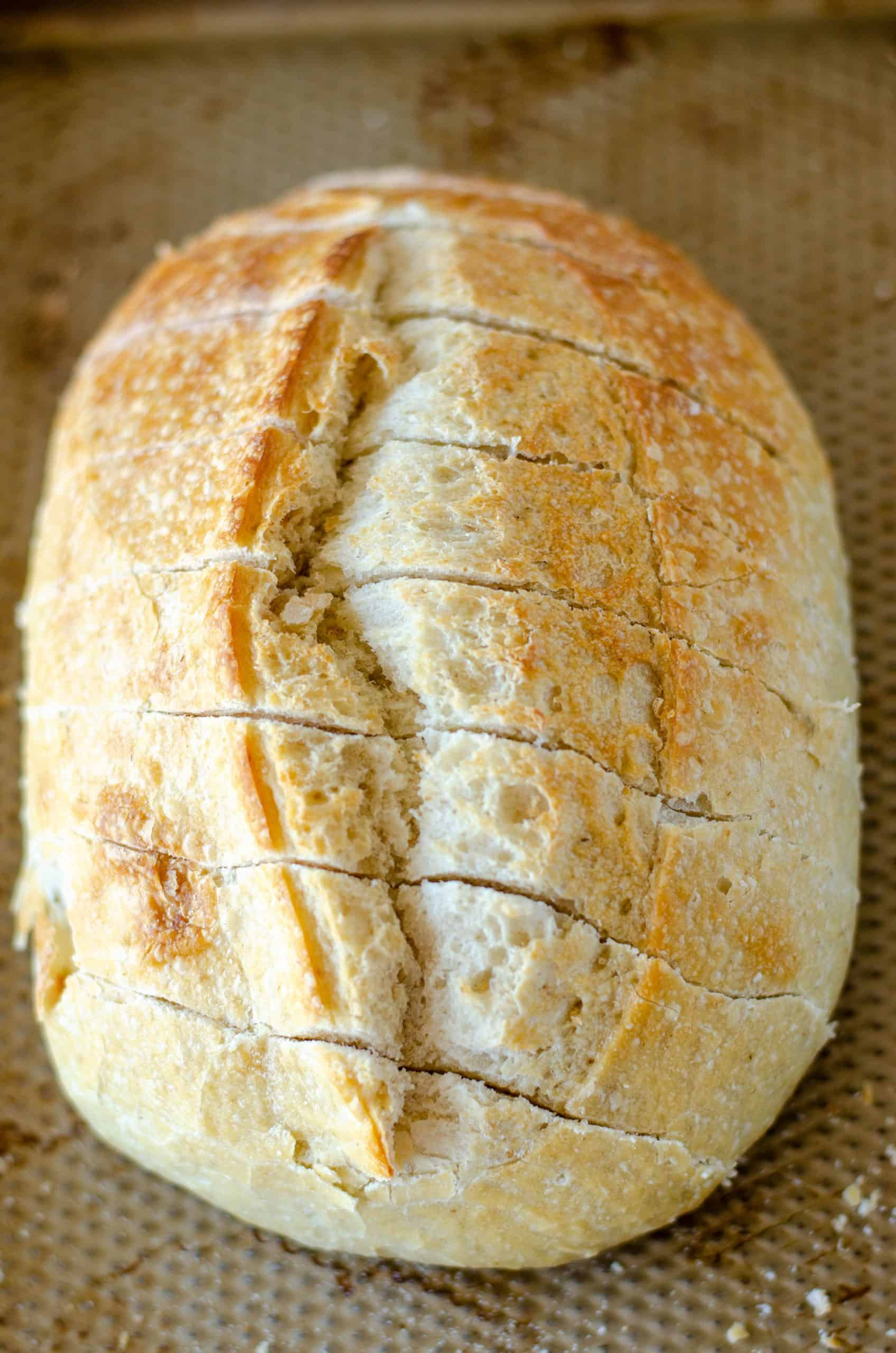 oval loaf of sourdough bread shown with diagonal cuts across it.