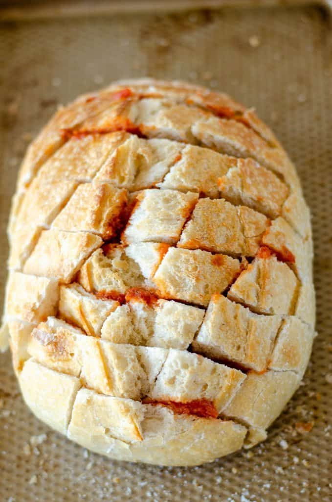 pizza sauce shown in the cuts of a sourdough bread