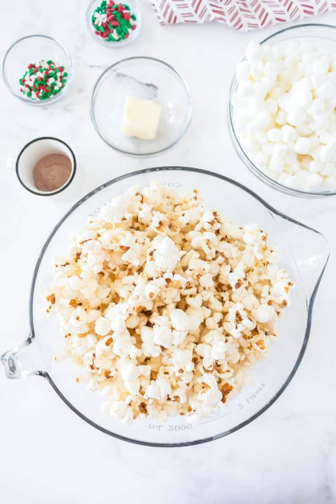 popped popcorn, butter, mini marshmallows, hot cocoa mix powder, Christmas sprinkles