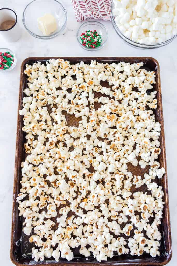 popped popcorn spread out onto butter coated baking sheet