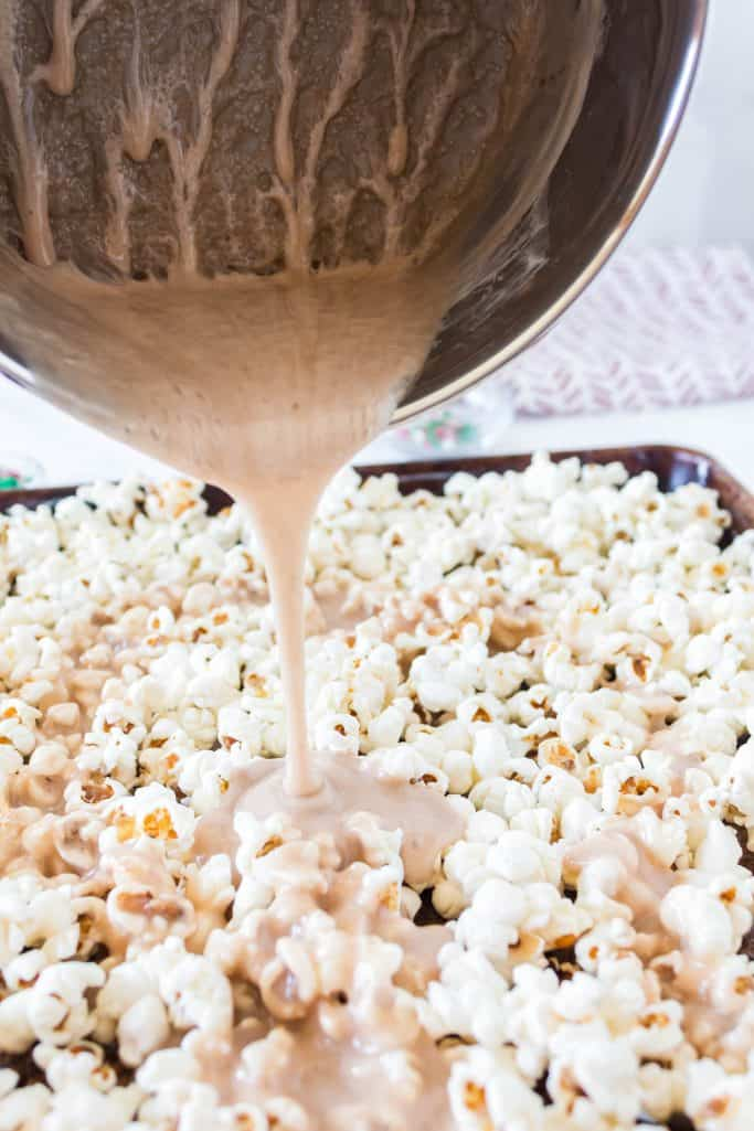pouring melted marshmallow mixture from a sauce pan onto popped popcorn