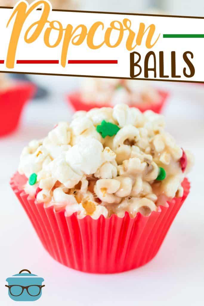 Receita fácil de bola de pipoca caseira de marshmallow do The Country Cook, uma bola de pipoca mostrada em um forro de cupcake vermelho com granulado de Natal