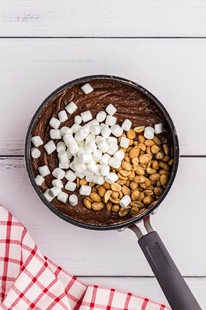 mini marshmallows and peanuts added to melted chocolate mixture in a sauce pan