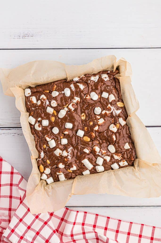 rocky road fudge batter poured into parchment paper lined baking dish