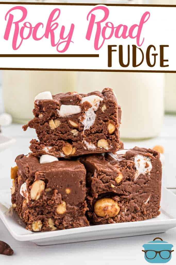 Homemade Rocky Road Fudge recipe from The Country Cook, fudge slices shown stacked on a white round plate with milk bottles in the background