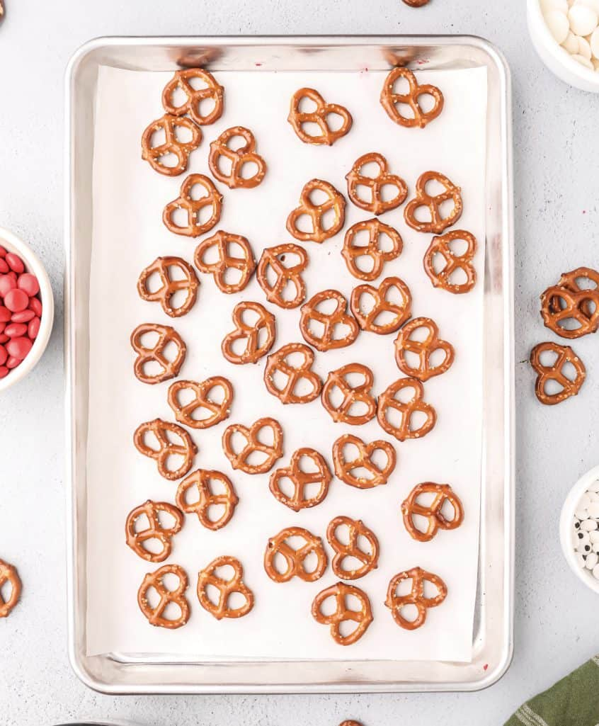 mini pretzels arranged in a single layer on a parchment lined baking sheet