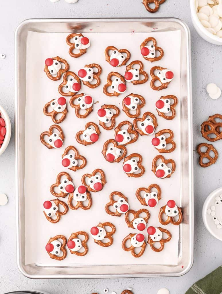 mini pretzels in a single layer with white chocolate dots and red m&m chocolate candies to make a reindeer looking pretzel on a baking sheet