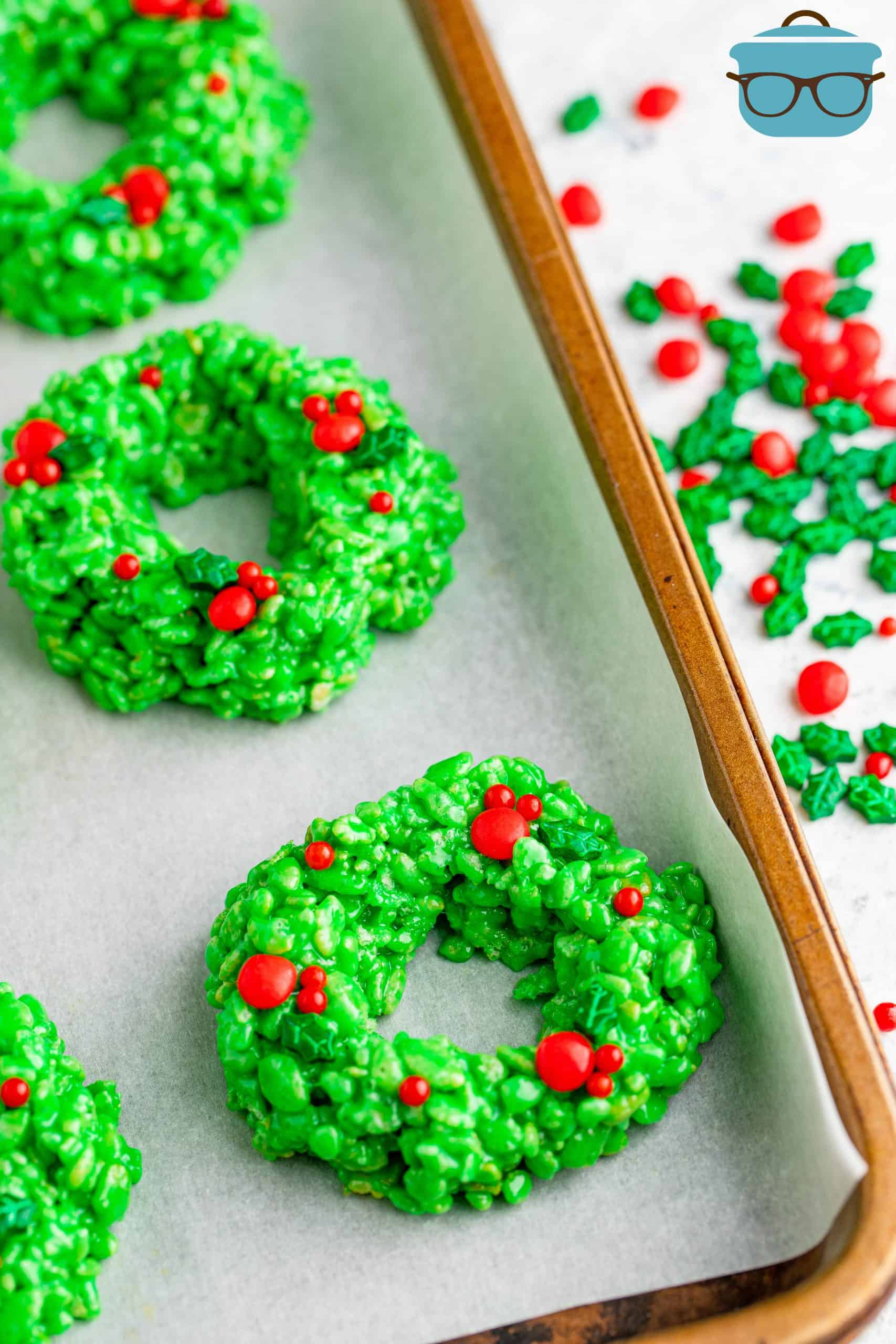 finished krispy wreaths on a baking tray lined with parchment paper.