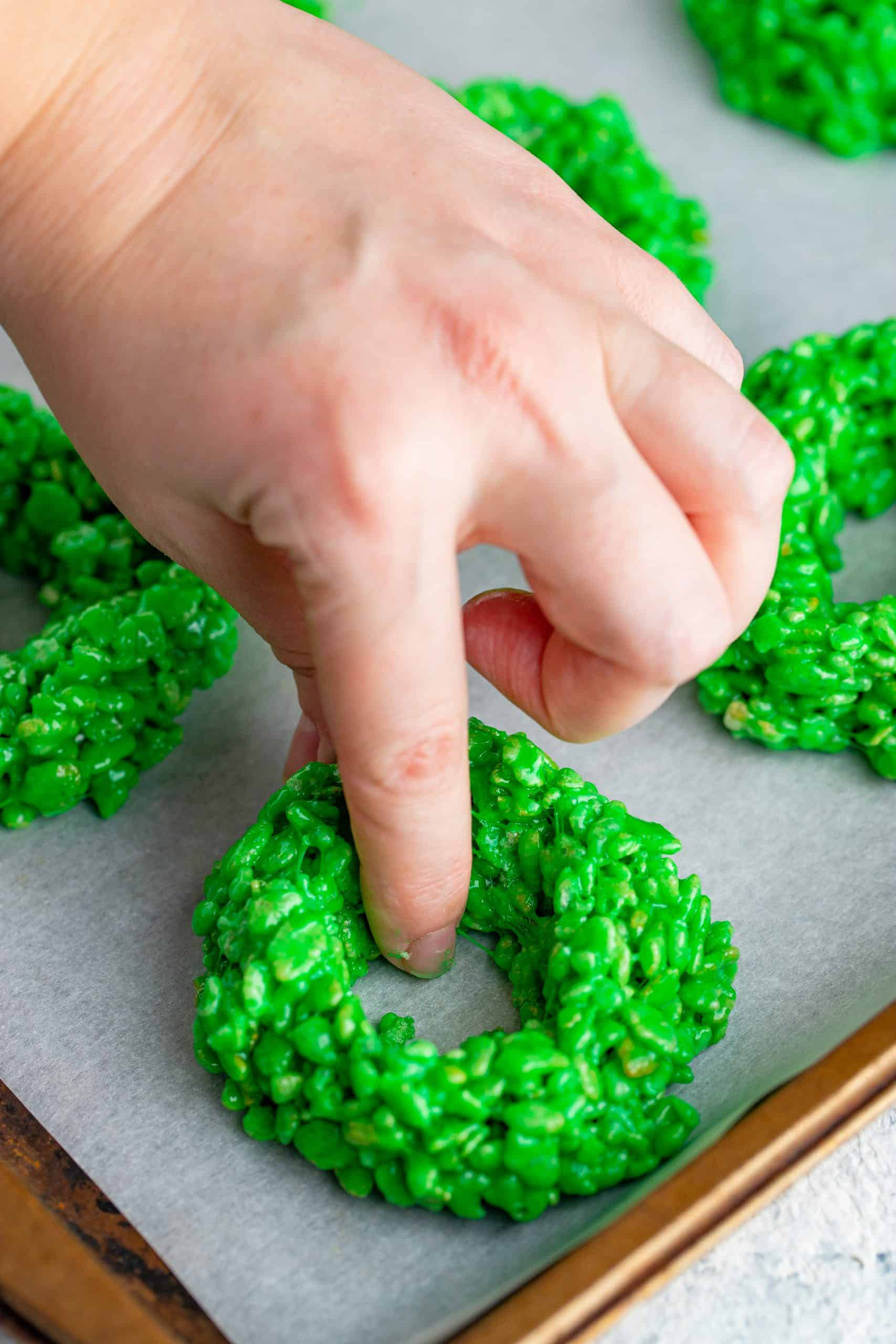 a hand making a whole inside the green krispy treat ball to make an open center.