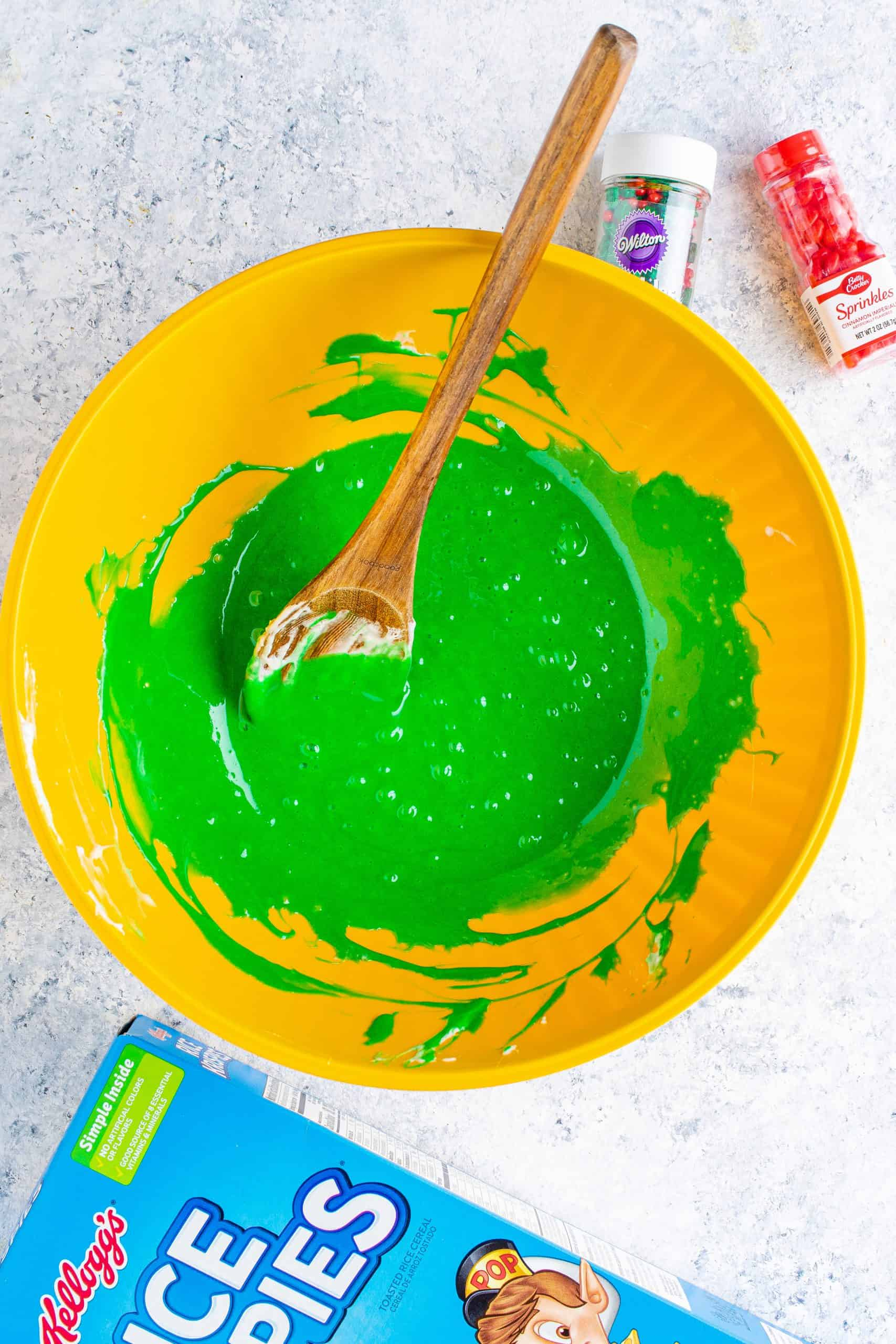 adding green food gel coring to melted marshmallows in a large yellow bowl and stirring with a wooden spoon.