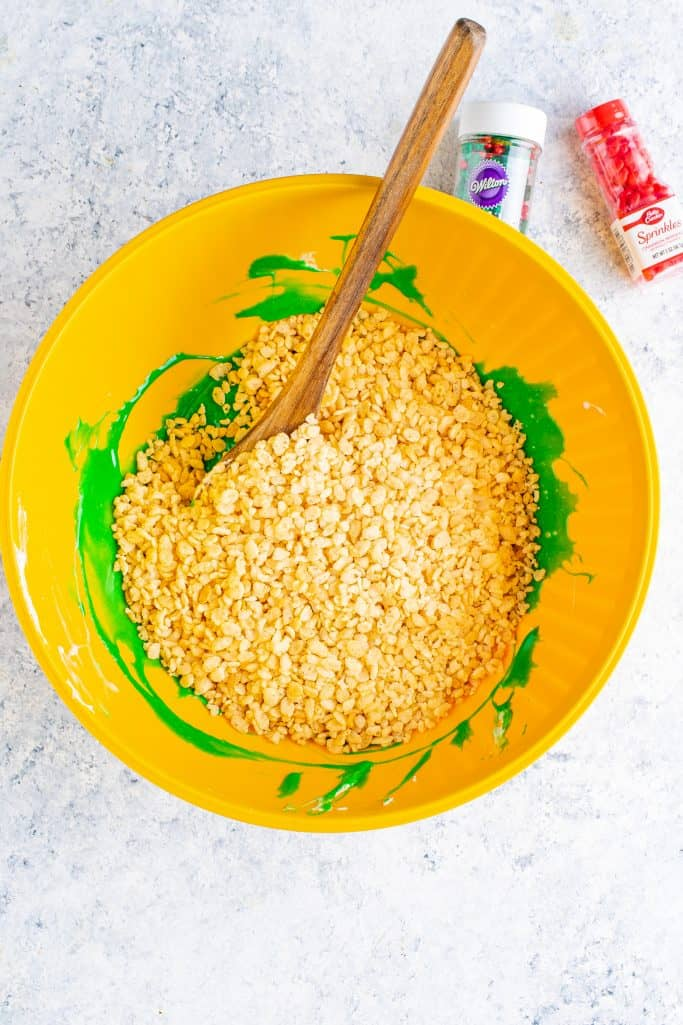 Rice Krispies cereal poured into yellow bowl with green colored melted marshmallows