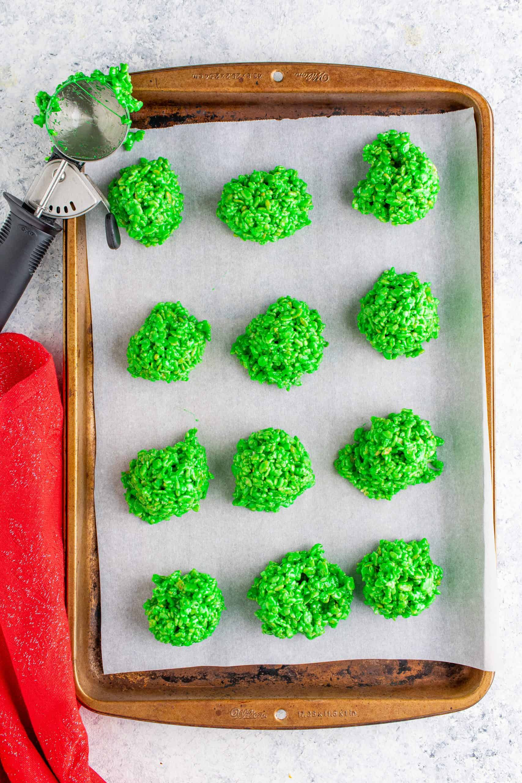 green balls of Rice Krispies cereal on a baking sheet lined with parchment paper.